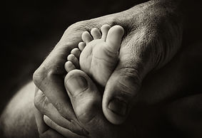 Man holding baby feet