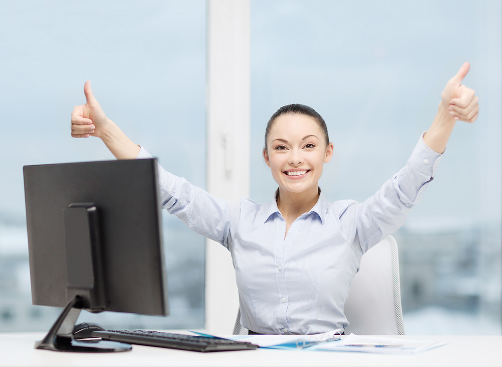 woman in front of a computer with two thumbs up