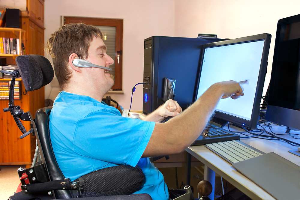 boy in wheelchair pointing at a computer screen