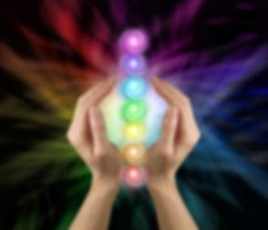 Sending the Seven Chakras Vortex Healing Energy - Female parallel hands against a multicoloured back