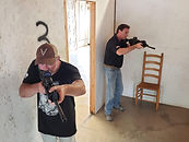 Two men with rifles working together to clear a room from agressors.