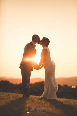 Kissing Bride and Groom at Sunset