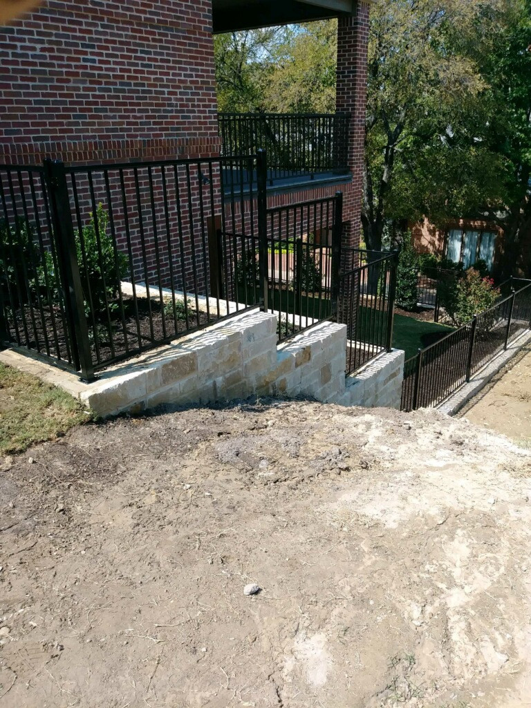 Custom Step Down Ornamental Iron with Stone Retaining Wall