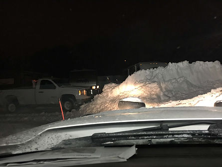 Piling up snow to remove it for a storage unit.