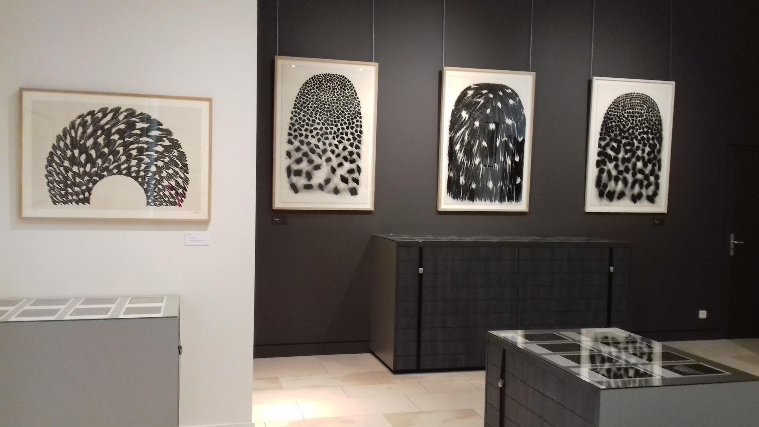 """Au mur, sérigraphies Arche (1999) et dessins Dôme (2000). Sous les vitrines livre """"Sur les traces d'Empedocle"""" (1992) : 60 gravures de Najia Mehadji et 60 poèmes de Pascal Amel."""
