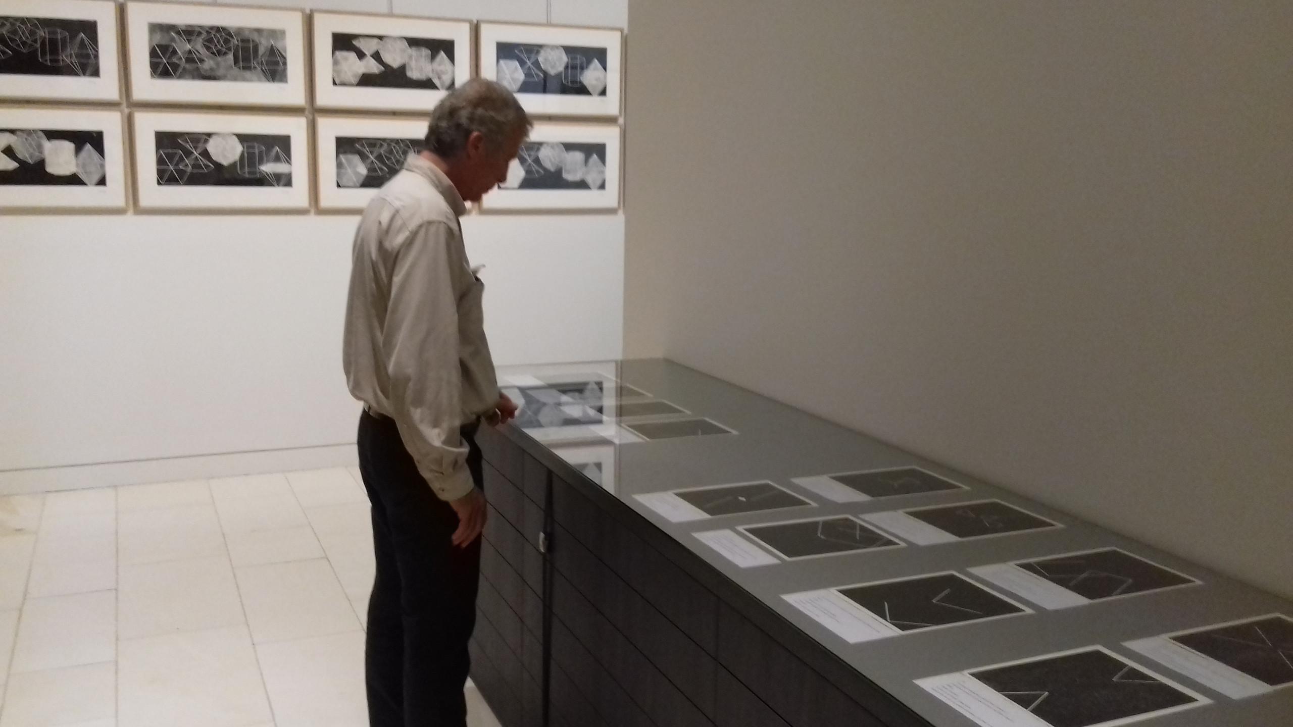 """Au mur les linogravures Polyèdres (1991) et Pascal Amel devant le livre """"Sur les trace d'Empedocle"""" (1992)"""