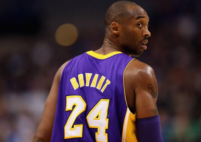 Kobe Bryant turns and look showing the #24 on his Laker purple road jersey