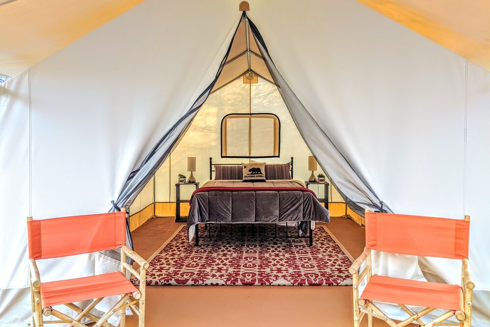 A bed and rug inside a safari tent at Wildhaven Sonoma, a Russian River glamping venue