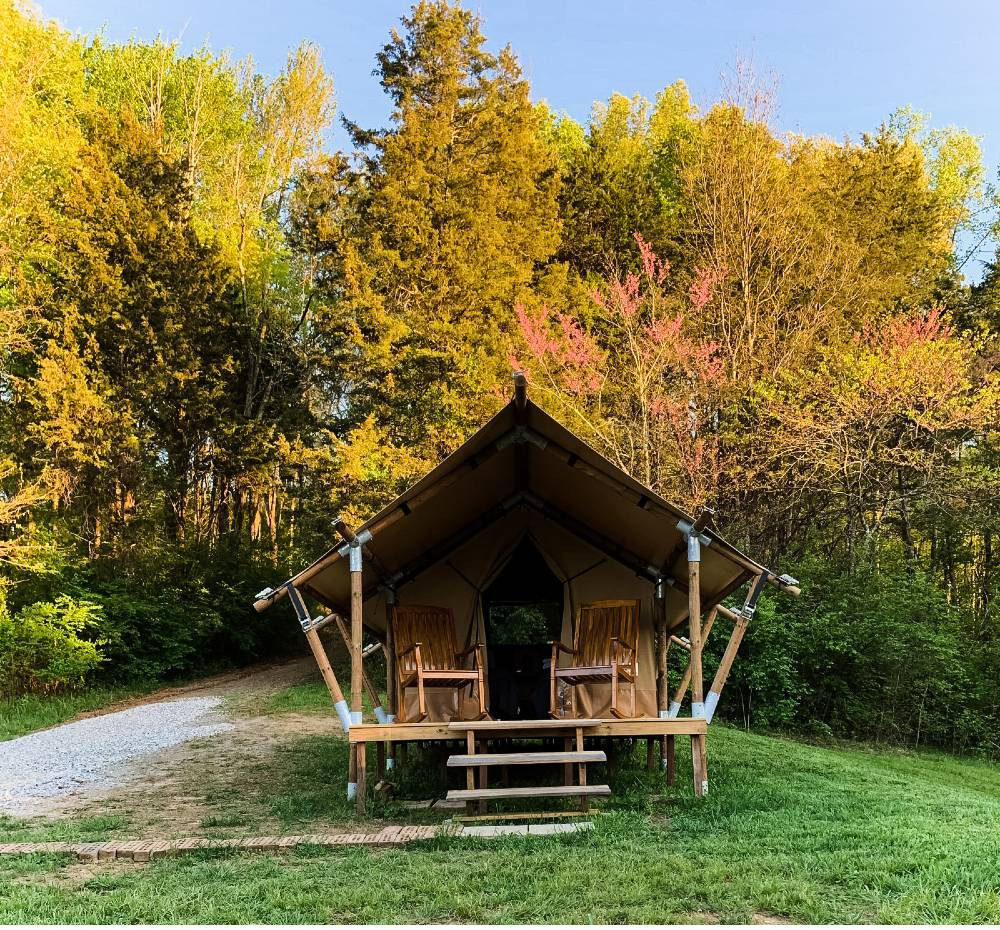 The front of an open tent at GlampKnox, a Tennessee glamping site, with rocking chairs on the front porch and changing leaves in the background