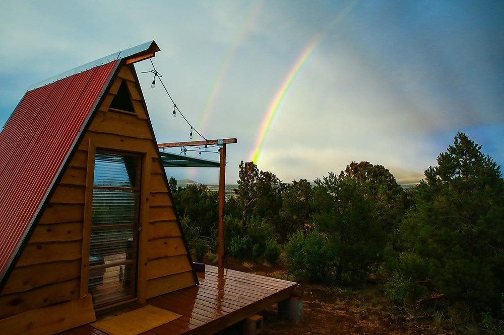 An A-frame cabin on a wooden platform with a rainbow in the sky and trees at Grand Canyon Eco Retreat