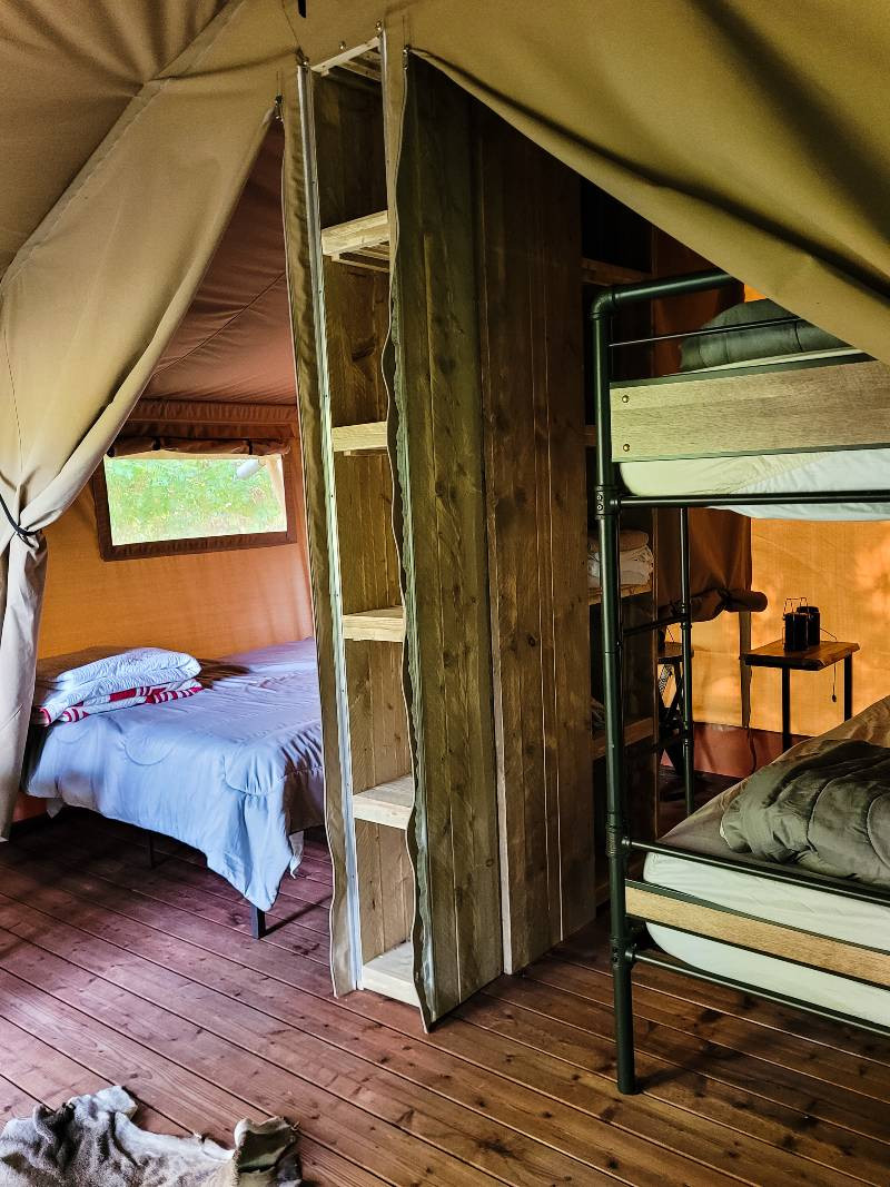 The interior of a tent at GlampKnox glamping in Tennessee, with three beds and a storage unit divider wall