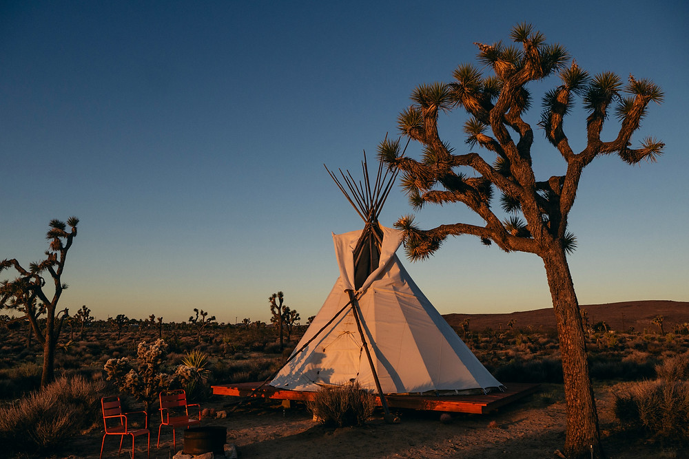 A tipi on a platform with chairs nearby in the desert at one of the glamping resorts in the Southwest