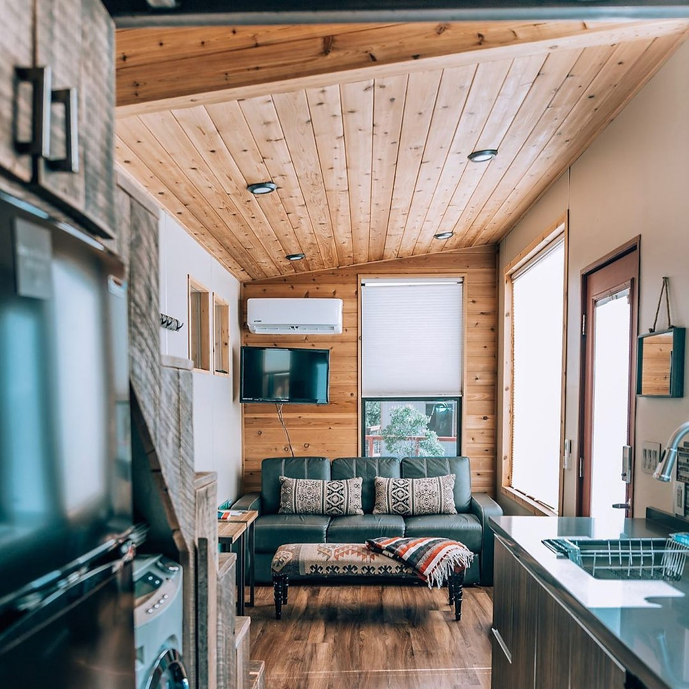 The inside of a tiny home at Tiny Camp Sedona, one of the best glamping resorts in the Southwest. Wooden walls and floors, refrigerator, couch with two pillows, a television, and more interior furnishings