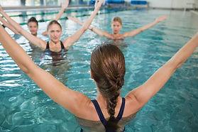 Smiling female fitness class doing aqua
