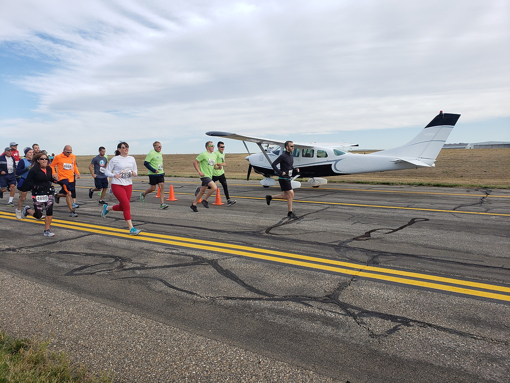 Runners running by one of the AFW planes