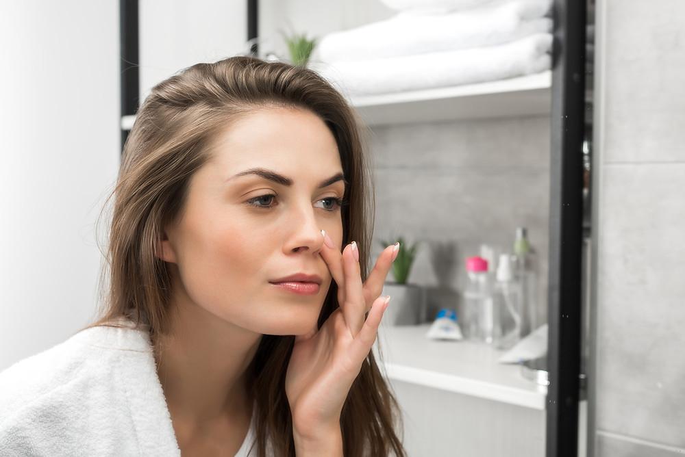 Mujer tocando su rostro frente a un espejo