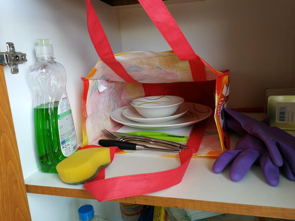 Fotografía de vajilla dentro de una bolsa de tela, con jabón lavaplatos y esponja en una gaveta.