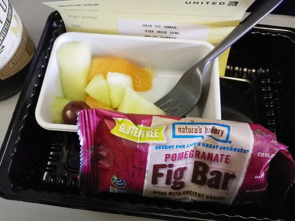 Desayuno de avión con frutas y una barrita.
