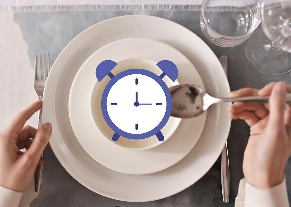 Plato con un reloj despertador encima