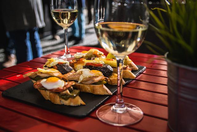 Fotografía de brusquetas en una mesa con copas de vino.