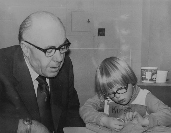 SACL founder Dr. John Dolan helps a child with an intellectual disability