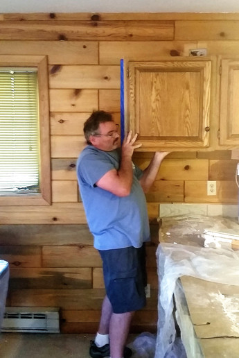 Measuring placement of new cabinetry.