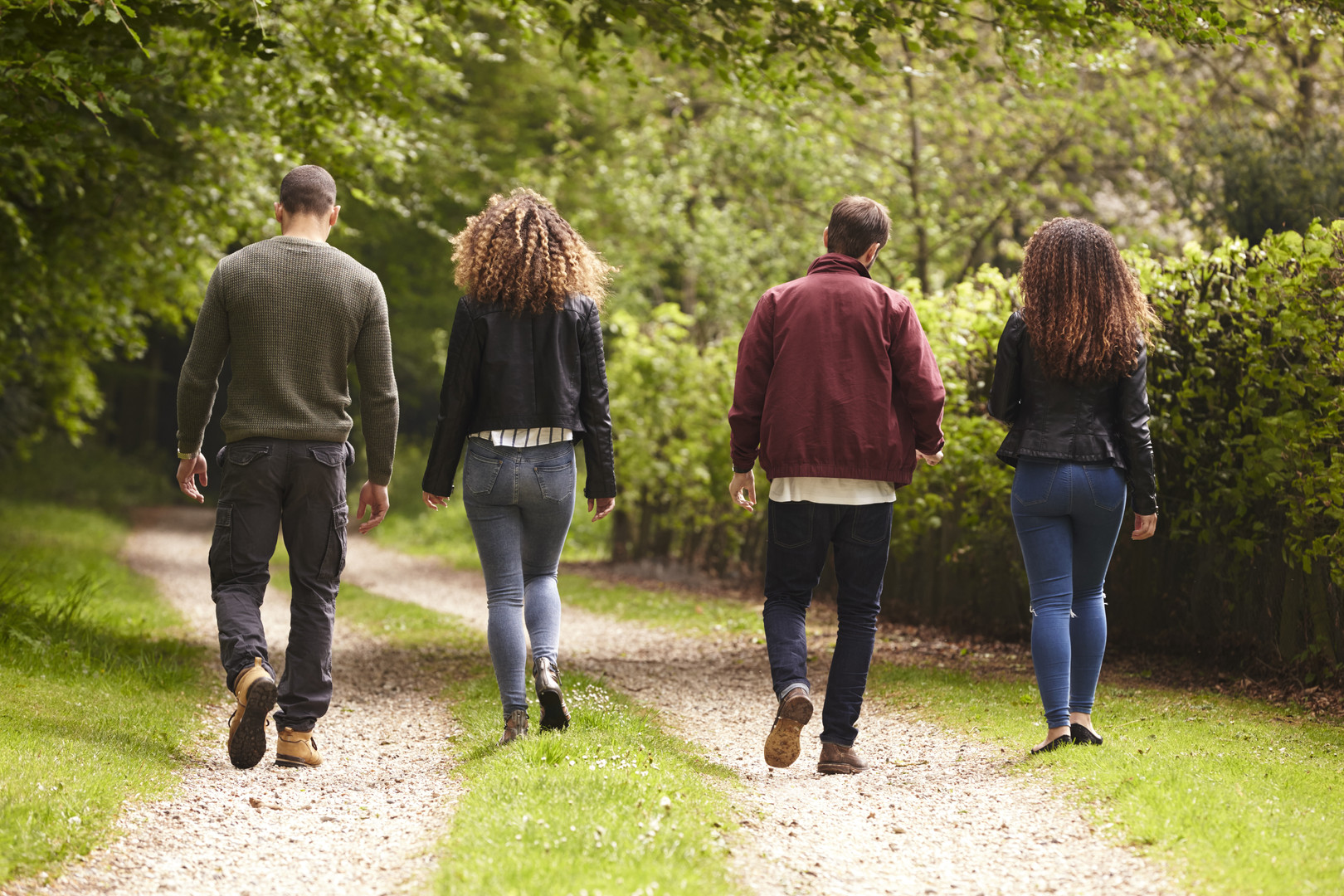 four-adult-friends-walking-down-a-countr