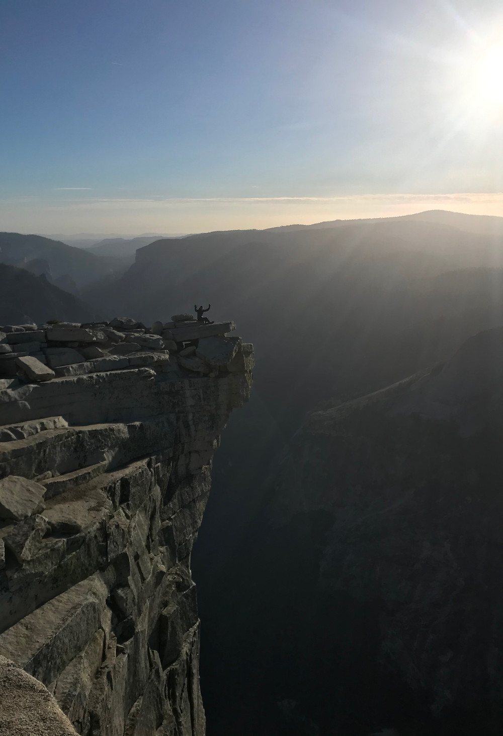 A man sitting on the edge of a cliff, hands up to celebrate the end of a long climb and sun rays shining down