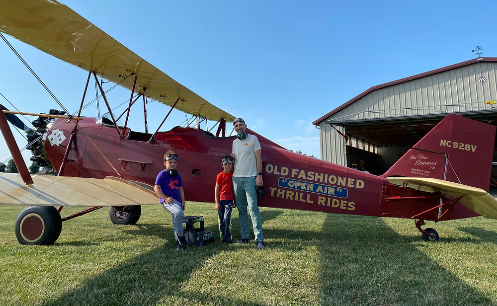 a man and his young sons stand in front of an old barnstoming airplane