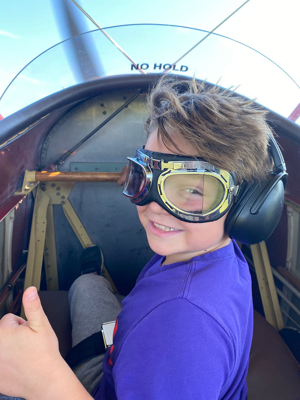 A young boy in a purple t shirt, with googles and headphones gives a thumbs up in the cockpit of a biplane.