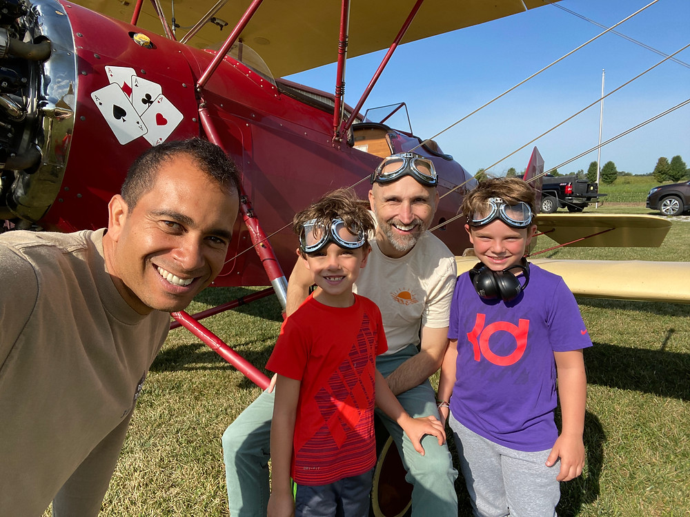 Logan and his boys pose with the owner of Goodfolk & O'Tymes Biplane Rides