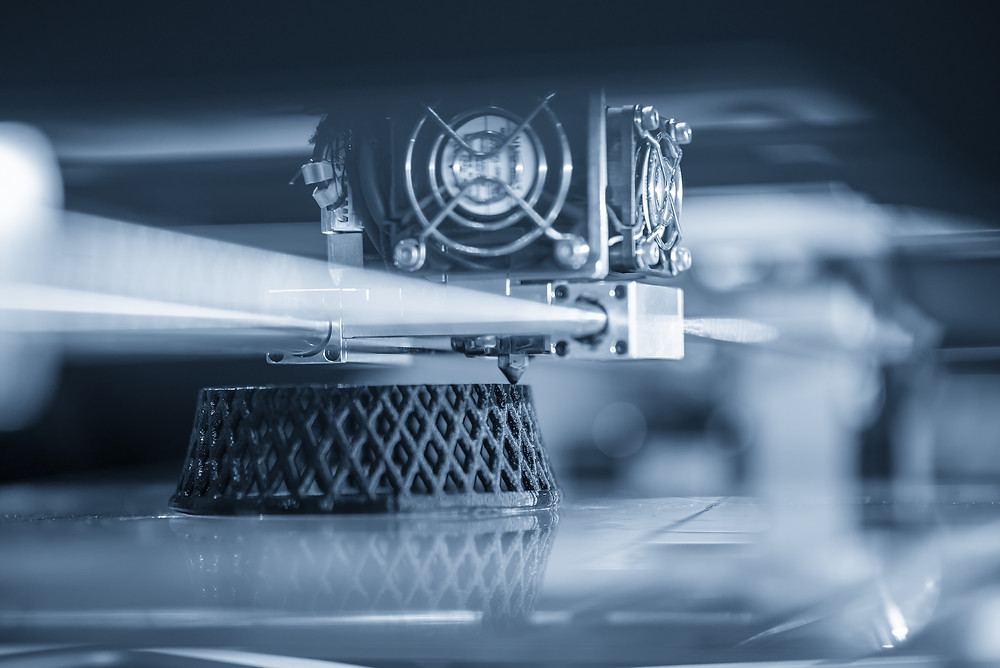 Monocolour photo of a 3D printer building a small support structure