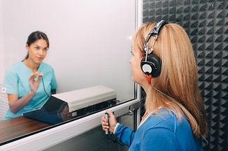 audiologist doing hearing exam to a matu