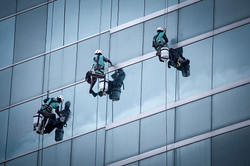 Group Of Workers Cleaning Windows Service On High Rise Building_edited