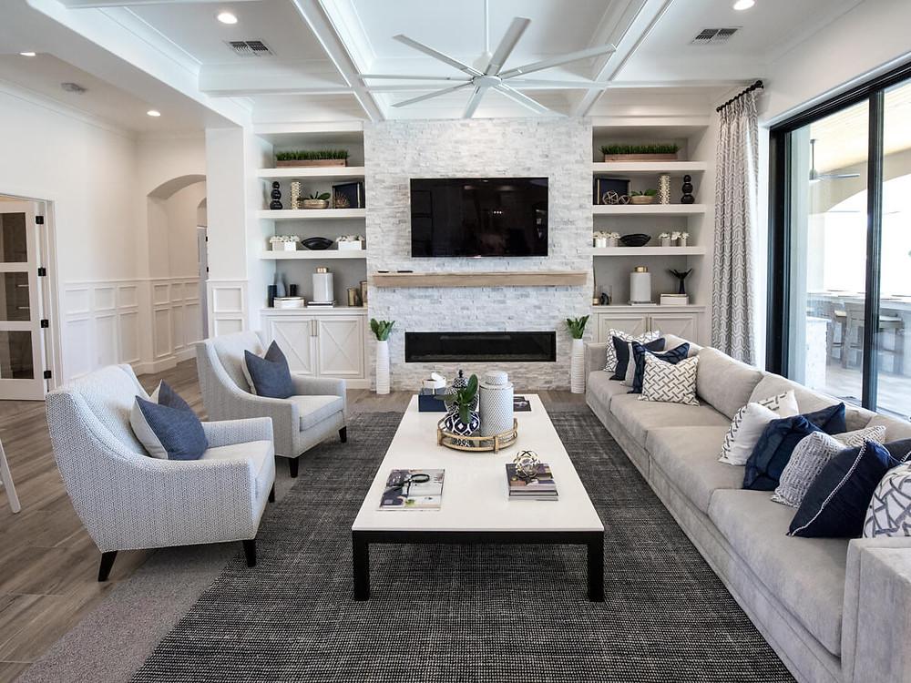 modern living room with box beam ceiling, stone wall, floor to ceiling window doors