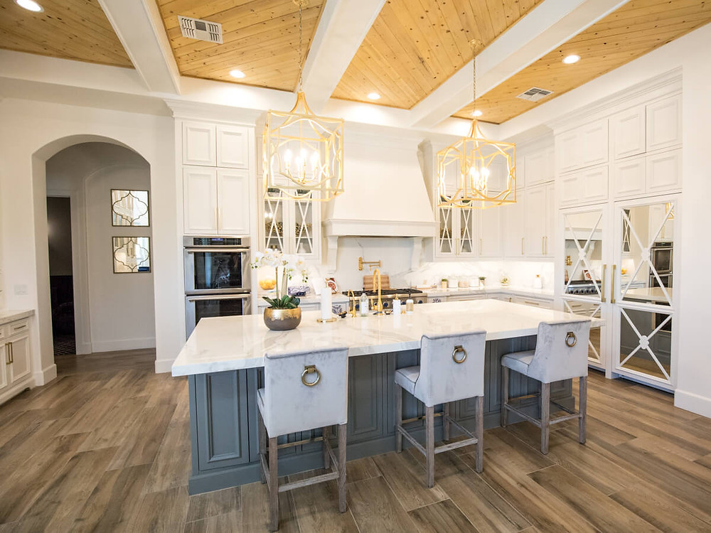 Traditional white kitchen with modern twist, gold fixtures, wood chevron ceiling