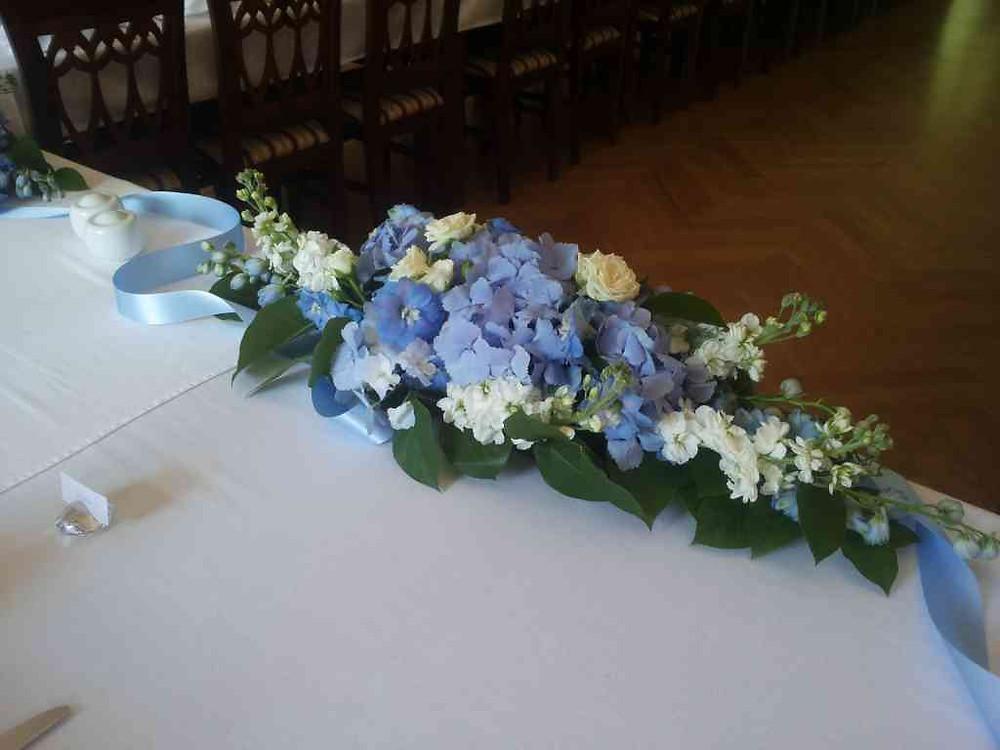 Svatební květinová aranž na stůl před novomanžele