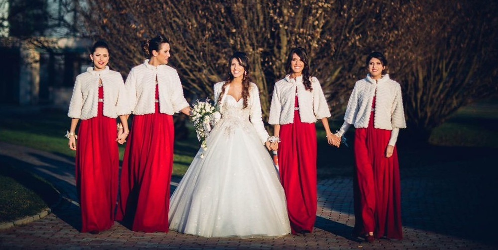 The red bridesmaids dresses are embellished with delightful ecru capes