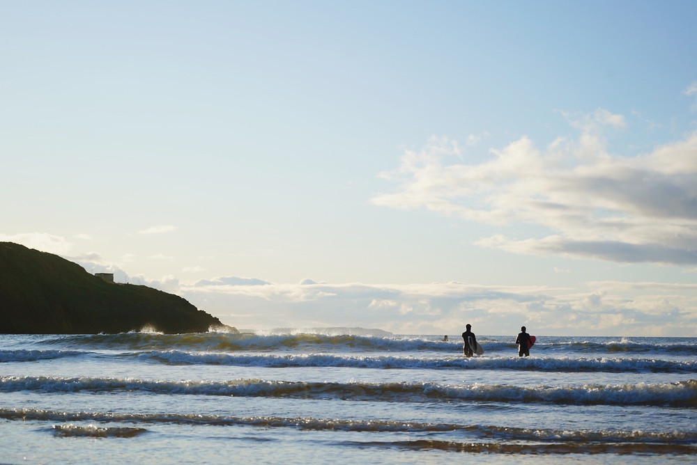surfers heading out