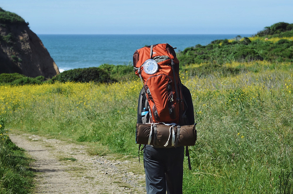 person backpacking near ocean