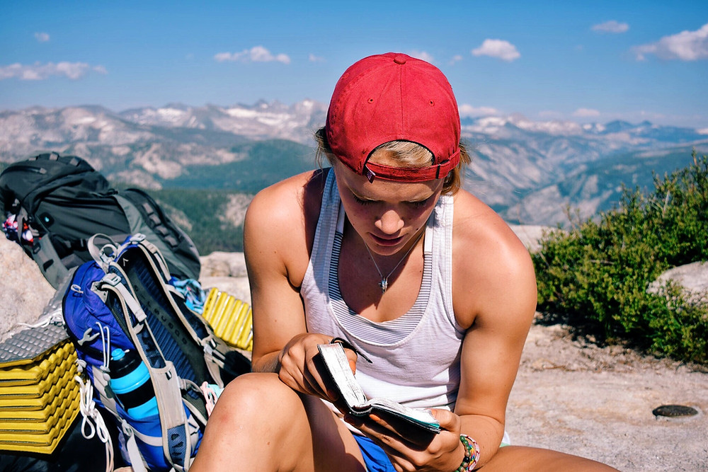woman reading with backpacking background
