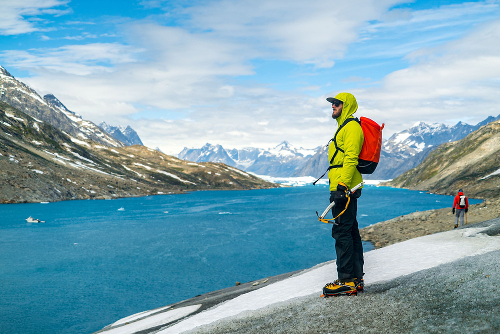 man with ice axe in front of water and mountains