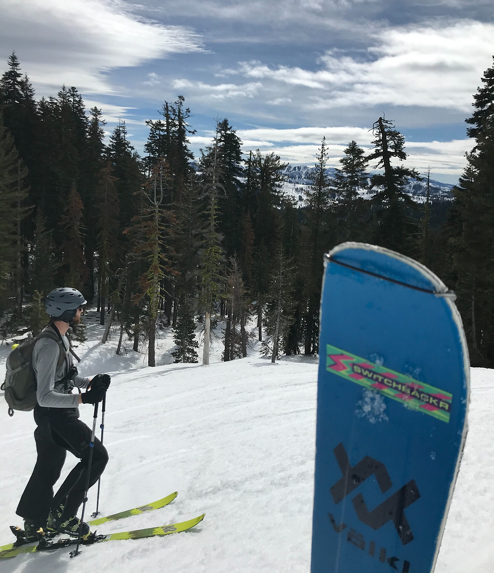 ski poking out of the snow with a skier in background