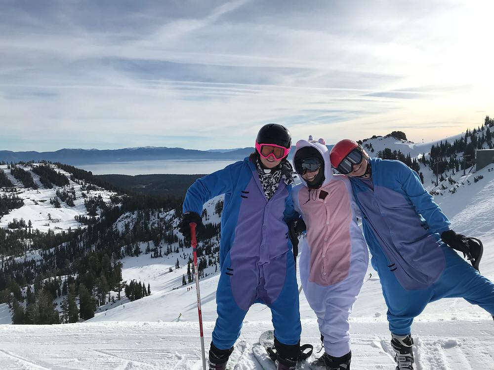three people in skis and onesies in front of lake tahoe