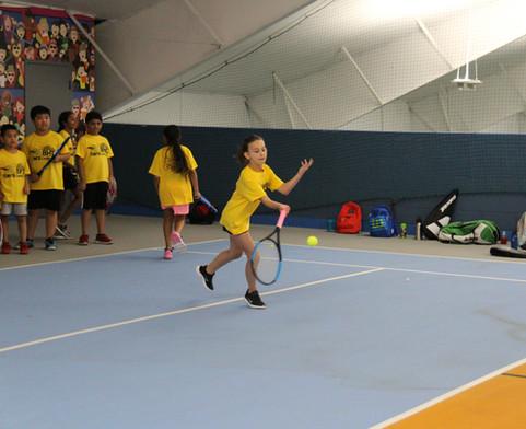 Girl hitting a tennis ball
