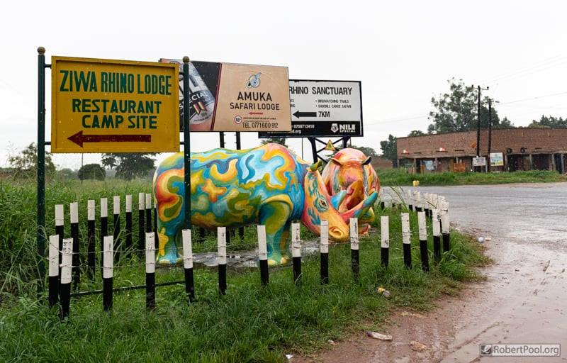 Brightly coloured full-size rhino statues at the turn-off to the Ziwa Rhino Sanctuary in Uganda
