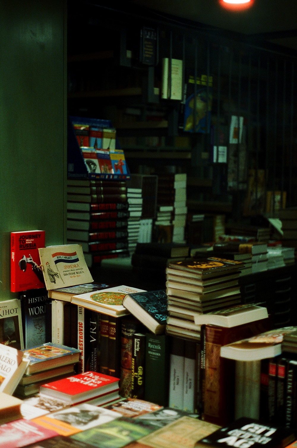 An image of the interior of a building, with several rows of cabinets covered with books. There are more filled bookshelves in the background and stacks of books in the foreground.