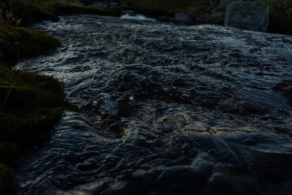 An image of a river at night. The water is not calm, but disturbed in many small ripples as it rushes past.