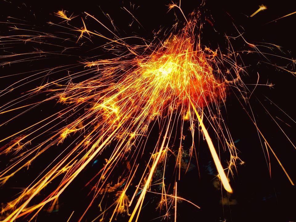 An image of a sparkler on a fully black background, shedding bright orange sparks everywhere.