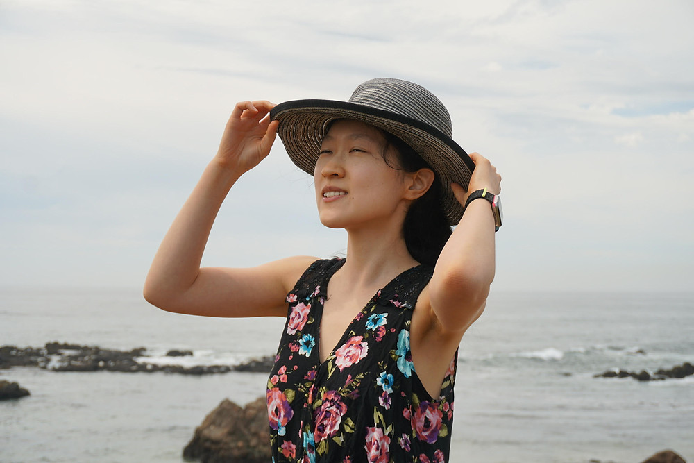 An image of Lucy Zhang, a light-skinned person in a sunhat and flowery sundress. She poses against a backdrop of the sea, smiling and looking upwards.